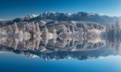 Symmetrical reflection, kaleidoscope. Natural abstract, panoramic landscape of snowy mountains and forest in sunny winter morning day with blue sky.