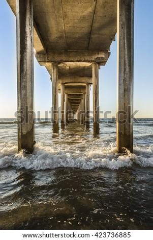 Symmetrical shot under Scripps Pier with waves during sunset in La Jolla, San Diego, California #423736885