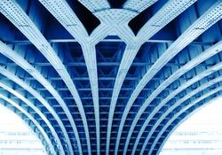 Symmetrical structure underneath a bridge. Blue steel construction. Bridge architecture background.