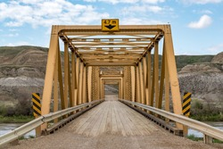 Symmetrical view of Highway 848 bridge crossing the Red Deer River west of Dorothy and southeast of Drumheller, Alberta, Canada in springtime