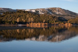 Symmetry in nature. Enchanting view of the Andes mountain range, forest and sky, and the reflection in lake Aluminé water surface at sunset, in Villa Pehuenia, Neuquén, Patagonia Argentina.