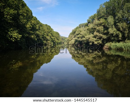 Symmetry in nature with reflections in the water. River Ter by Girona, Catalonia, Spain in the spring. Green trees, full vegetation on the riverbank.