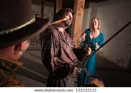 Sympathetic lady watches man get hit by mace in medieval battle