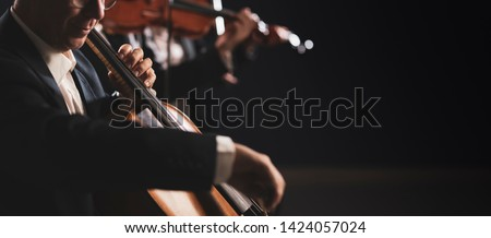 Symphonic orchestra performing on stage and playing a classical music concert, cellist in the foreground, arts and synergy concept Stockfoto ©