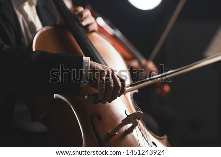Symphonic orchestra performing on stage and playing a classical music concert, cellist in the foreground, hands close up Stockfoto ©