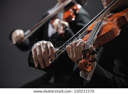 Symphony music, violinist at concert, hand close up