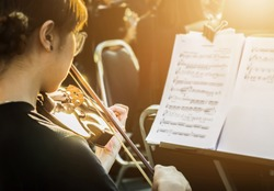 Symphony orchestra on stage, hands playing violin. Shallow depth of field, Public place.