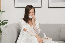 Symptoms of allergic rhinitis in women. Sick woman in white nightwear with a cold blowing her nose into a tissue paper at home. Cold weather allergies