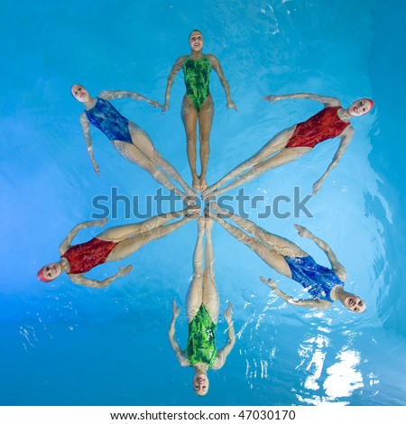 Synchronized swimmers hold pose for camera