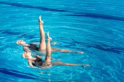 Synchronized swimming pair performing in a swimming pool