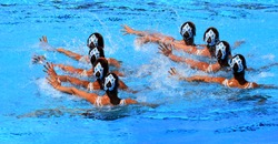Synchronized swimming team performing a synchronized routine of elaborate moves in the water.