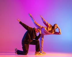 Synchronous movements. Two young people, guy and girl, dancing contemporary dance over pink background in neon light. Modern dance aesthetics concept