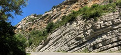 Syncline of sedimentary rocks by the side of a road in southern France under the blue sky of a bright, Sunny summer's day with trees and shrubs. Ancient geology. Our world in times gone by.