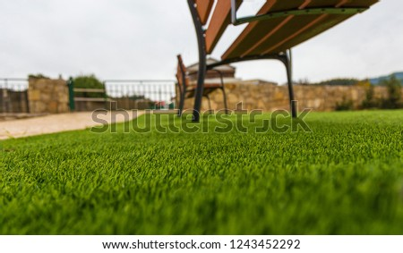 Synthetic Grass On a Park With Benches on a Pale Blue Sky #1243452292