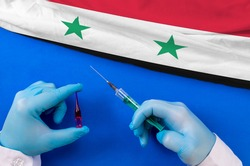 Syria Vaccination. Hands of doctor holding syringe and coronavirus (COVID-19) vial vaccine on flag Syria