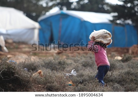 Syrian refugee little girl took bread from charity to tent. Foto stock ©