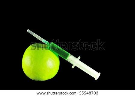 Syringe and green apple on black background