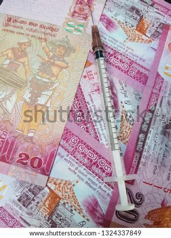 Syringe placed on Sri Lanka banknotes.Use for website/banner background, backdrop, montage menu #1324337849