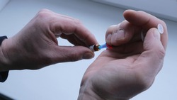syringe with red liquid in male hands against the background of a white surface, pulling the drug from the capsule into the syringe close-up, a bright red substance for injection fills the syringe