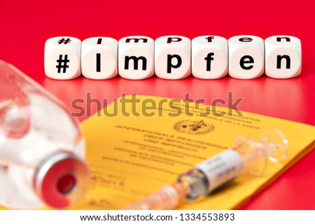 Syringe with vaccine and International Vaccination Passport. Vaccination written with dice. (Impfen german word for Vaccinate) #1334553893