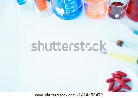 Syringes and pills taken with medical instruments and beakers, multi-colored liquid science laboratories on the operating table for a chemical background