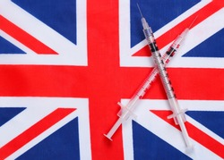 Syringes with the flag of Great Britain. Vaccination. Pandemic covid-19