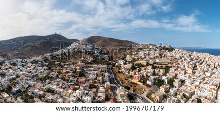 Syros island, Greece, Cyclades capital Ermoupolis cityscape panorama, Ano Siros or Syra town panoramic aerial drone view, cloudy blue sky background. Travel destination Foto stock ©