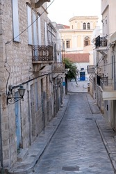 Syros island Hermoupolis village Cyclades destination Greece. Above view of cobblestone empty narrow alley traditional old stonewall buildings at famous Ermoupoli capital of Syra summer day. Vertical