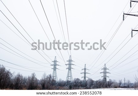 System of electricity pylons and power lines out-of-town in the winter day.