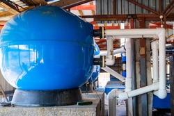 System pumping water for agriculture. Big blue extension tanks with PVC pipes water system