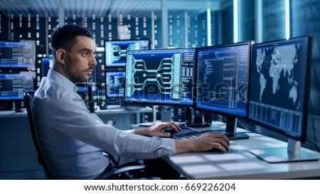 Photo of  System Security Specialist Working at System Control Center. Room is Full of Screens Displaying Various Information.