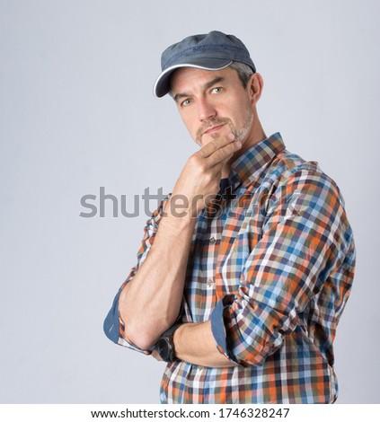 Szakállas 40 éves sportos Férfi kockás ingben és baseball sapkában gondolkodik, kezével az állához ér, semleges háttér elött fotózva. Stock fotó ©