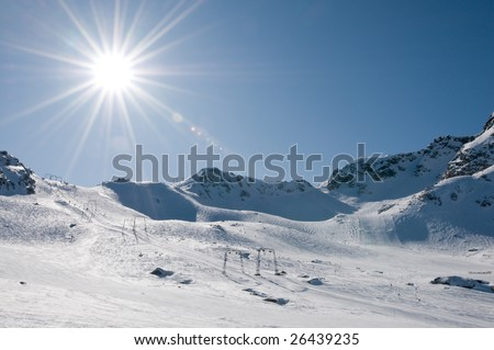 T-bar ski lift at high altitude alpine resort, direct sun with flare