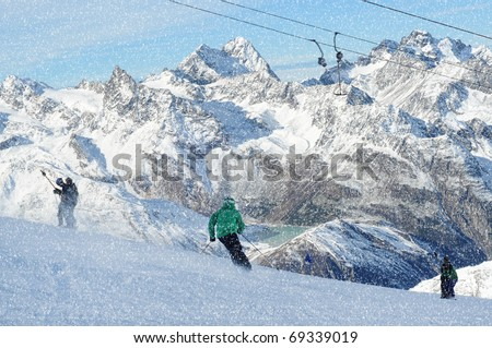 T bar ski lift pulling skiers up the slope. Skier skiing down the slope. Snowy winter in European Alps.