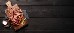 T-bone grilled beef steak with spices and herbs on wide wooden background. Top view flat lay with copy space