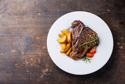 T-Bone Steak with roasted potato wedges on white plate on wooden background