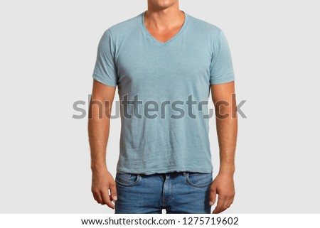T shirt design and advertisement concept. Unrecognizable man with muscular body wears casual blue t shirt and jeans, dressed casually, copy space for your advertisement or promotional content