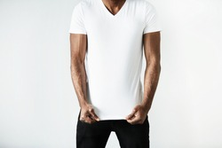 T-shirt design and advertising concept. Cropped studio shot of dark skinned young male posing against white copy space wall wearing white T-shirt with copy space for your promotional content