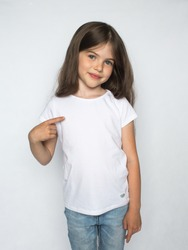 t-shirt design concept - smiling little girl in blank white t-shirt pointing at herself