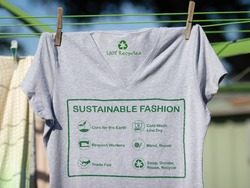 T shirt on washing line with sustainable fashion label, care for the earth, respect for workers, trade fair, mend and repair, reuse, swap or donate with icons.