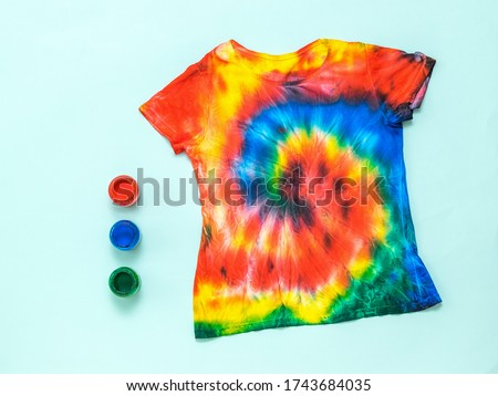 T-shirt painted in the style of tai Dai on a light pastel background. White clothes painted by hand. Flat lay. Place for text.