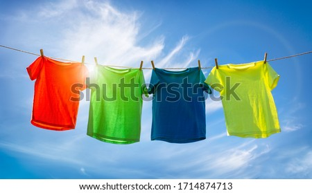 Photo of  T-shirts hanging on a clothesline in front of blue sky and sun