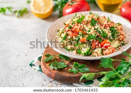Tabbouleh salad - traditional Middle Eastern or Arabic cuisine. Levantine vegetarian salad with bulgur, quinoa, tomato, cucumber, parsley and lemon juice. Tabbouleh with bulgur closeup
