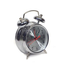 Table alarm clock in silver stainless steel body with a round shape of the dial, showing five minutes past ten isolated on a white background side view closeup
