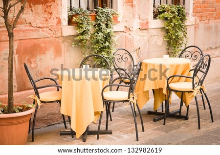 table and chairs at a restaurant in italy