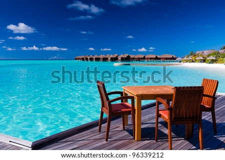 Table and chairs at tropical beach restaurant