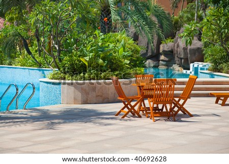 Table and chairs by a swimming pool in the garden