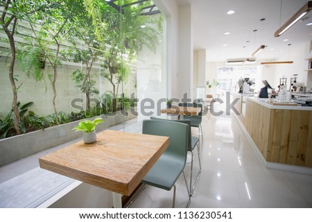 Table and chairs in the coffee shop with sunlight and trees. #1136230541
