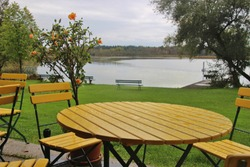 Table and chairs on the Lido of  Ibm lake, or Heratinger lake, in Upper Austria, in autumn. It's rainy weather. A nature reserve next to the Ibm moorland.  Ibm, Upper Austria, Europe.