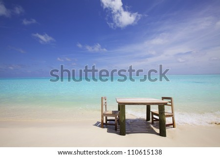 Table and chairs on white sand beach with blue ocean, white clouds and blue sky
